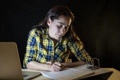 Överansträngd och tröttad studentkvinna som sent studerar på natten på svart bakgrund Arkivfoton