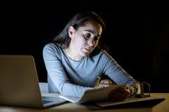Överansträngd och tröttad studentkvinna som sent studerar på natten på svart bakgrund Royaltyfri Bild