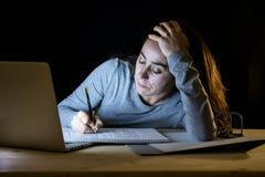 Överansträngd och tröttad studentkvinna som sent studerar på natten på svart bakgrund Royaltyfri Fotografi