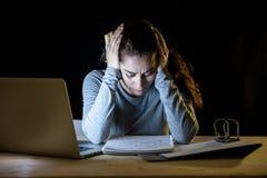 Överansträngd och tröttad studentkvinna som sent studerar på natten på svart bakgrund Arkivbild