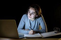Överansträngd och tröttad studentkvinna som sent studerar på natten på svart bakgrund Arkivfoto
