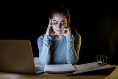 Överansträngd och tröttad studentkvinna som sent studerar på natten på svart bakgrund Royaltyfria Bilder