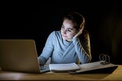 Överansträngd och tröttad studentkvinna som sent studerar på natten på svart bakgrund Royaltyfria Foton