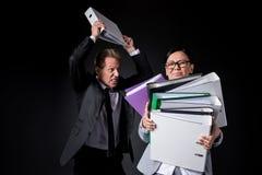 Överansträngde hållande mappar för mogen affärskvinna medan ilsken manlig kollega som är i stånd till att slå royaltyfri fotografi