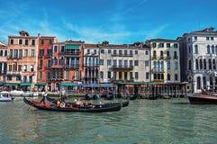Överblick av byggnader, pir och gondoler framme av kanalen som är stor på Venedig Arkivbild