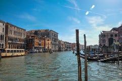Överblick av byggnader, pir och gondoler framme av kanalen som är stor på Venedig Royaltyfria Bilder