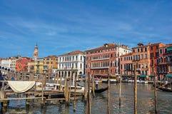 Överblick av byggnader, pir och gondoler framme av kanalen som är stor på Venedig Arkivfoton