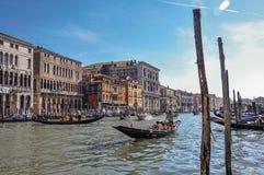 Överblick av byggnader, pir och gondoler framme av kanalen som är stor på Venedig Fotografering för Bildbyråer