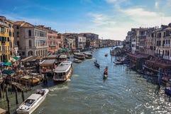Överblick av byggnader, pir och gondoler framme av kanalen som är stor på Venedig Arkivbilder