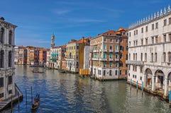 Överblick av byggnader, pir och gondoler framme av kanalen som är stor på Venedig Royaltyfria Foton