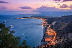 Överblick av den Taormina kustlinjen på skymning Royaltyfri Foto
