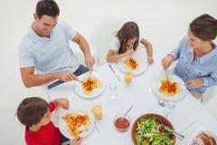 Överblick av en familj som äter pasta med sås och sallad royaltyfria foton