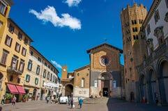Överblick av en fyrkant med den gammalt byggnader, kyrkan och folk under en blå himmel i Orvieto arkivbilder