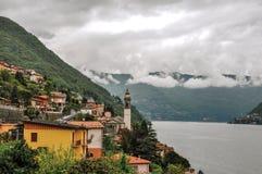 Överblick av sjön Como med berg och byar i en molnig regnig dag, nära Como fotografering för bildbyråer