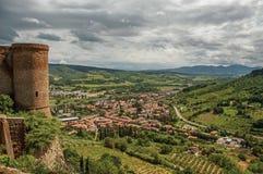 Överblick av stentornet, gröna kullar, vingårdar och stadtak nära en väg Från centret av Orvieto royaltyfri foto