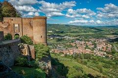 Överblick av stentornet, gröna kullar, vingårdar och stadtak nära en väg Från centret av Orvieto royaltyfria bilder