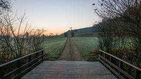 Överbrygga att leda in i ett fält med en orange himmel i bakgrunden Fotografering för Bildbyråer