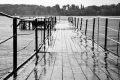 Överbrygga sträckning in i floden, regnet, det våta brädet och järnräcke, utsikt, på horisonten, skogen, droppar arkivbilder
