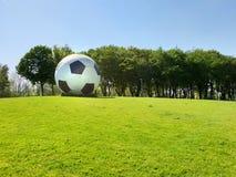 Överdimensionerad fotboll som ett konstverk gör mellanslag offentligt fotografering för bildbyråer