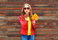 Överför den nätta unga kvinnan för mode luft den söta kyssen med gula lönnblad i höstdag över träbakgrund som bär rött läder royaltyfri bild