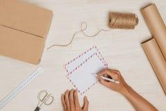 Överföring av ett brev Flygpostkuvert på den wood tabellen Arkivfoton