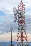 Överföringslinjer som passerar till och med TV-sändningtorn Satellit- skiva som monteras i mikrovågantennen Träelektrisk stolpeco royaltyfri fotografi