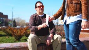 Överföringsmutor i gatan En man ger pengar i ett kuvert till en annan man, medan sitta på bänken i, parkerar lager videofilmer