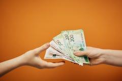 Överföringspengar till varandra, två händer och kassa på orange bakgrund royaltyfri foto