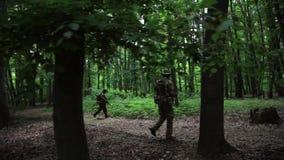 Överfalla från bakhåll partisan- krigare för gerillasoldaten som går i skog, att bära deras vapen stock video