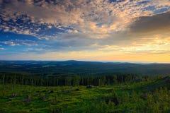 Överflödande morgonsoluppgång i det Sumava berget, hugger av ner skogen på kullen, trevliga moln på himlen, Knizeci Stolec, tjeck Arkivfoton