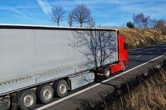 Övergående landskap för röd lastbil Arkivfoto