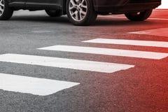 Övergångsställe vägmarkering och rörande bil Arkivbild