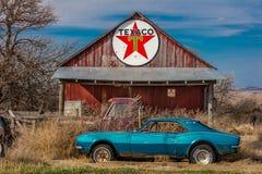 Övergav blåa Camaro Chevrolete framme av den öde Texaco stationen, avlägsen del av Nebraska Royaltyfria Foton