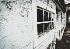 Övergav byggnader på sidan av en väg med brutna fönster Royaltyfri Fotografi