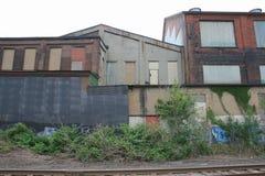 Övergav fabriks- byggnader med målade lager och som stiger ombord upp Windows bak drevspår med molnig himmel Royaltyfri Foto