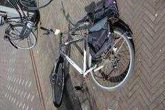 Övergav och gamla cyklar på gatan som markeras med etiketten som ska tas bort av kommunen av Den Haag i Nederländerna royaltyfri fotografi