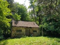 Övergav små stenar huset i mitt av en grön skog royaltyfria foton