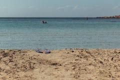 Övergav strandsandaler framme av en grekisk strand Royaltyfri Foto