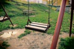 Övergav tomma gungor på en ensam lekplats parkerar in utomhus, inga barn Royaltyfria Bilder