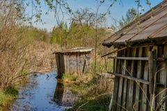 Övergav trädgårdtäppor på våren Kollapsade träbyggnader Royaltyfri Foto