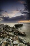 Överge den konkreta strukturen längs kusten över solnedgångbakgrund och det dramatiska molnet arkivfoto
