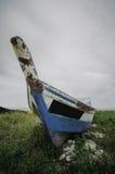 Överge det blåa fiberfartyget som strandas på kusten med mjuka och dramatiska moln royaltyfria foton
