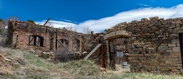 Överge stenbyggnader i en Colorado spökstad med varningssi royaltyfria foton