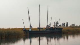 Övergett fiska segelbåten på sjön på rainny dag arkivbilder