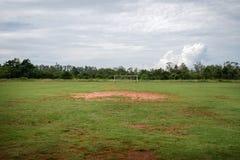 Övergett fotbollfält med inget och mycket dåligt gräs arkivbild