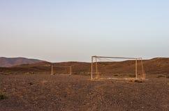 Övergett fotbollmål i öknen på solnedgången arkivbilder