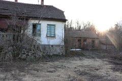 Övergett gammalt hus och stall för gård i bergen i hösttid arkivfoto