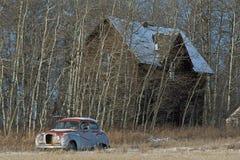 Övergett gammalt lantbrukarhem och gammal bil Royaltyfria Bilder