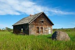 Övergett hus i gräs- fält Arkivbilder