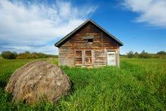 Övergett hus i gräs- fält med höbalen framme Arkivfoto